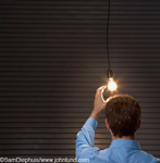 Businessman reaching for light bulb